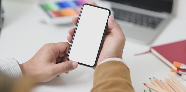 Vista do close-up do empresário segurando o smartphone de tela em branco no local de trabalho mínimo
