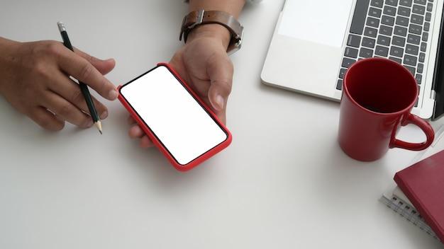 Vista do close-up do empresário usando o telefone em sua sala de escritório moderno