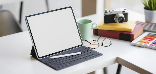 Vista do close-up do espaço de trabalho de design confortável com tablet digital de tela em branco e material de escritório