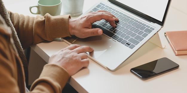 Vista do close-up do freelancer masculino trabalhando em seu projeto enquanto estiver digitando no computador portátil