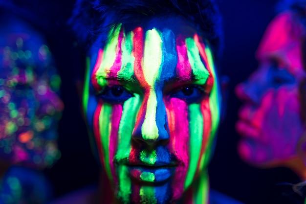 Vista do close-up do homem com maquiagem fluorescente