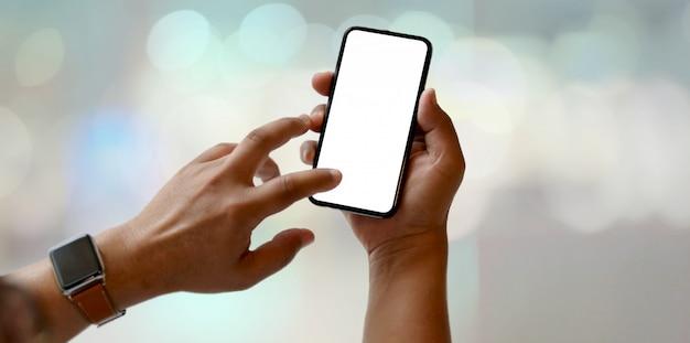 Vista do close-up do homem segurando o smartphone de tela em branco