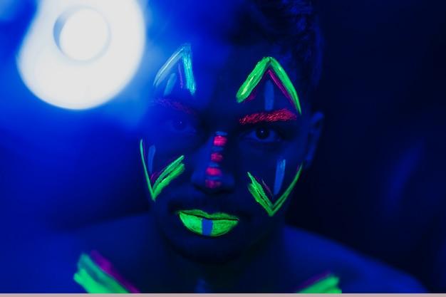 Vista do close-up do homem usando maquiagem fluorescente