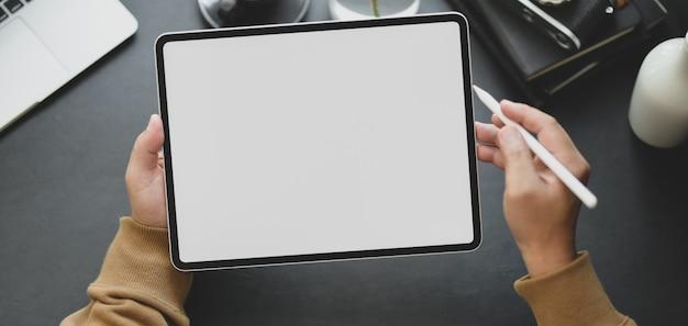 Vista do close-up do homem usando o tablet de tela em branco enquanto trabalhava no local de trabalho moderno escuro