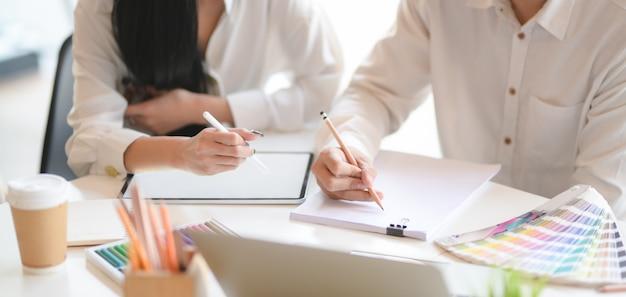 Vista do close-up do jovem designer profissional discutindo o projeto juntos enquanto estiver usando o tablet de tela em branco