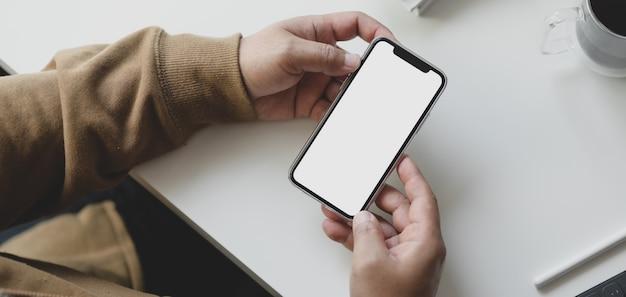 Vista do close-up do jovem freelancer masculino procurando informações no smartphone