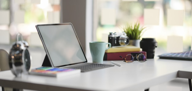 Vista do close-up do local de trabalho de design confortável com tablet de tela em branco e material de escritório