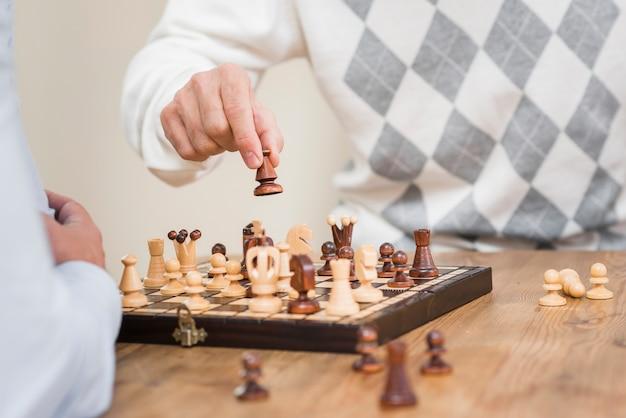 Vista do close-up do pai mão e tabuleiro de xadrez na mesa