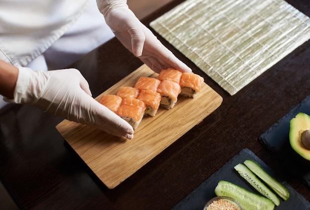 Vista do close-up do processo de preparação de sushi rolante. chef está servindo pãezinhos deliciosos na tábua de madeira