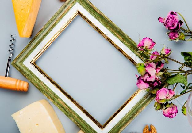 Vista do close-up do quadro com saca-rolhas de queijo e flores ao redor em branco, com espaço de cópia