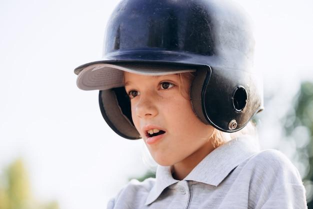 Vista do close-up, uma garota bonita em um capacete, pensamento focado