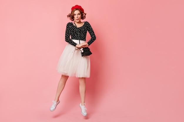 Vista do comprimento total da alegre garota francesa na boina vermelha. mulher jovem elegante com saia branca exuberante, olhando para a câmera.