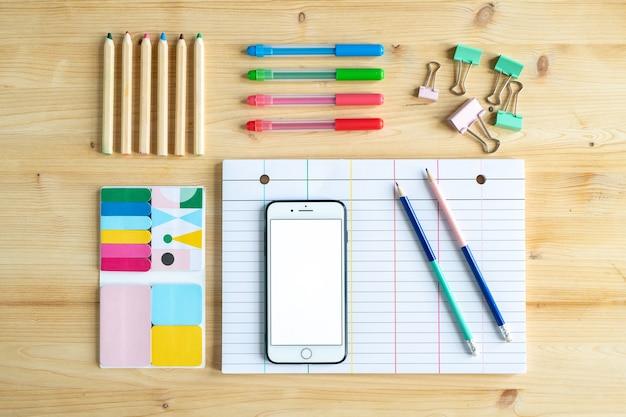 Vista do escritório ou material educacional na mesa de madeira - vários conjuntos de giz de cera, smartphone, clipes e papel pautado