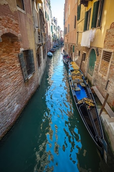 Vista do estreito canal com barcos e gôndolas em veneza