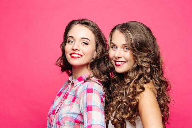 Vista do estúdio de garotas bonitas com magníficos cabelos ondulados e lábios vermelhos