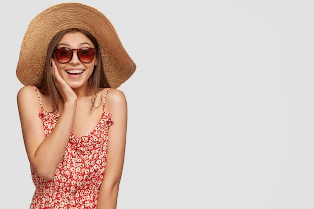 Vista do estúdio de uma mulher alegre com um sorriso dentuço, usando óculos escuros da moda, chapéu de palha