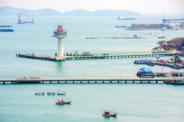 Vista do farol e do porto de ko sichang com navio de transporte e barco local com o mar bonito da costa leste da tailândia.