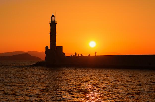 Vista do farol no mar em chania, creta, grécia. silhuetas contra o pôr do sol.