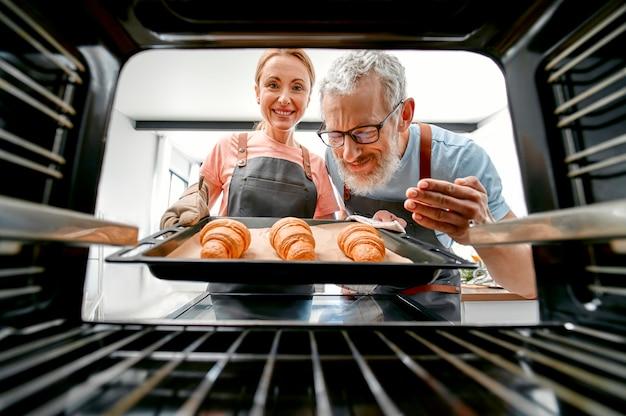 Vista do forno casal sênior maduro retire uma assadeira com croissants perfumados.