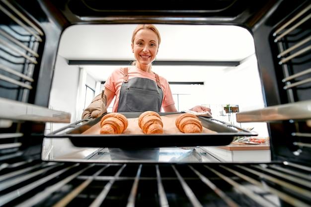Vista do forno, uma linda mulher de avental segura uma assadeira com croissants.