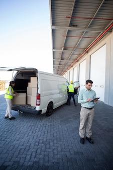 Vista do gerente está usando um tablet na frente dos trabalhadores estão carregando um caminhão