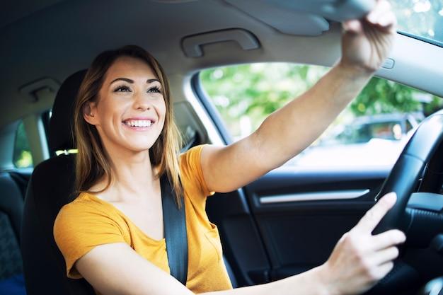 Vista do interior do carro de uma mulher motorista ajustando os espelhos antes de dirigir um carro