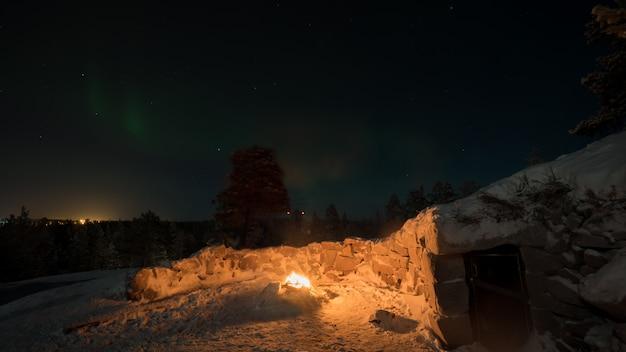 Vista do inverno do fogo perto da cabana e luzes do norte no céu escuro da noite, finlândia