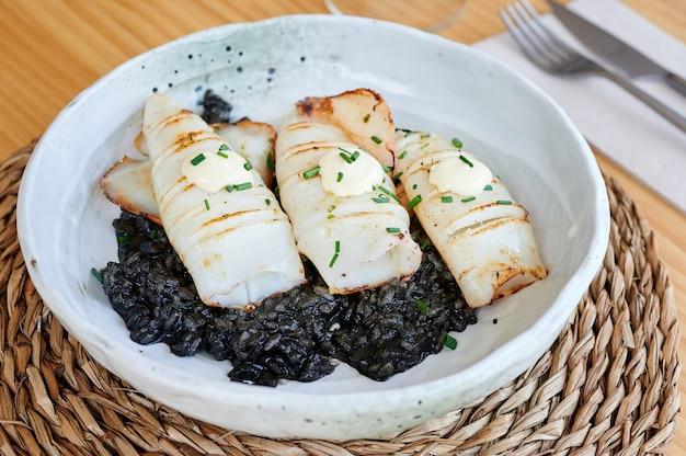 Vista do jantar de um prato de lulas bebê grelhadas sobre arroz preto