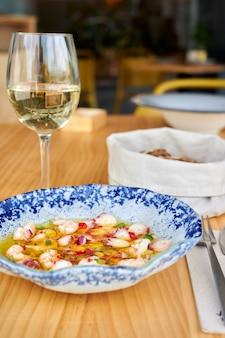 Vista do jantar em uma mesa de restaurante com um prato fresco de salada de frutos do mar, uma taça de vinho branco e uma cesta de pães