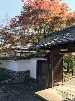 Vista do lado ao portão de entrada de madeira no templo japonês tradicional
