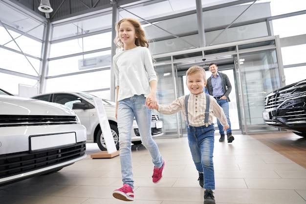 Vista do lado da sorrir duas crianças indo no salão de automóvel grande