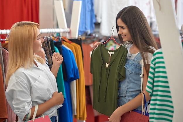 Vista do lado de dois amigos, escolhendo roupas na loja