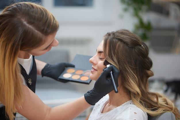 Vista do lado do maquiador fazendo rosto para mulher no salão de beleza