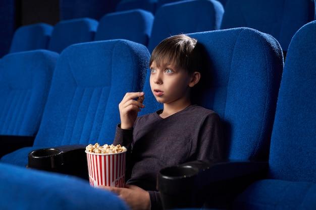 Vista do lado do menino excitado com olhos grandes e boca aberta que olha o filme surpreendente no cinema.