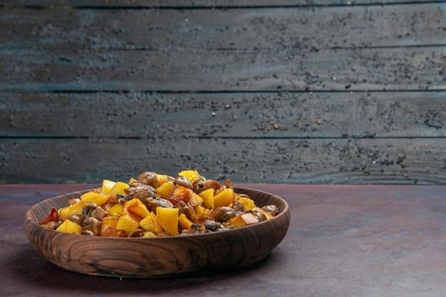 Vista do lado esquerdo batatas fritas com purê de cogumelos com batatas em uma tigela no fundo escuro