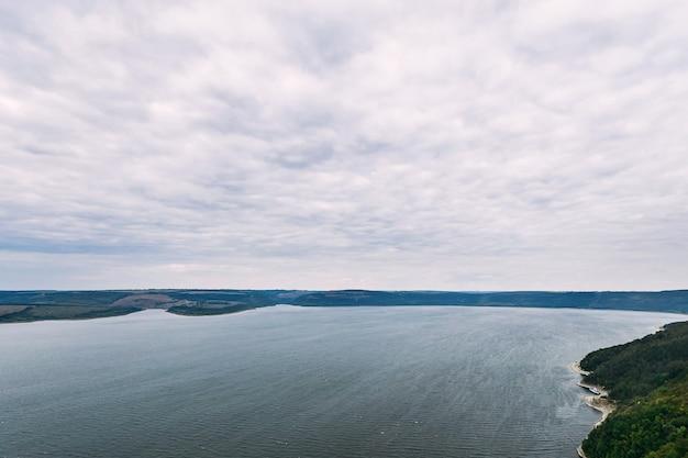 Vista do lago no tempo escuro com nuvens cinzentas no céu