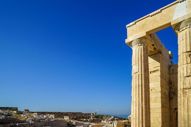 Vista do local de arqueologia grega e fachada de propylaea, porta de entrada para a acrópole construída com mar