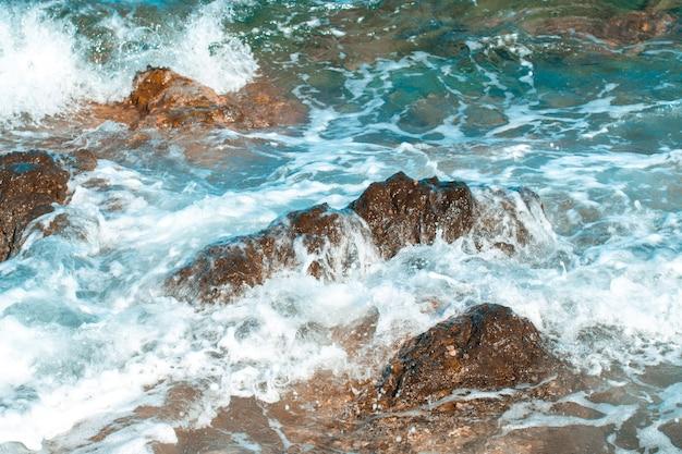 Vista do mar azul com ondas e pedras