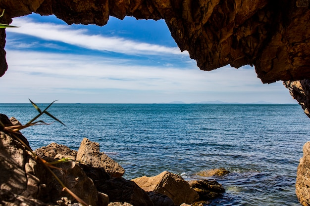 Vista do mar azul, do céu azul e da nuvem branca do furo da rocha em tailândia.