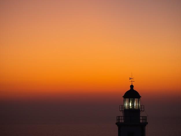 Vista do mar com a silhueta de um farol ao pôr do sol