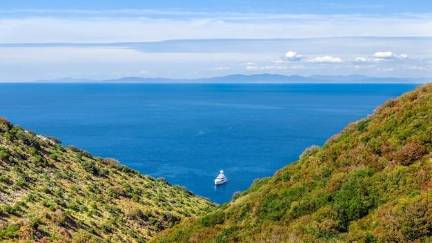 Vista do mar com barco no mar. vista através de duas colinas formando um triângulo com a linha do horizonte