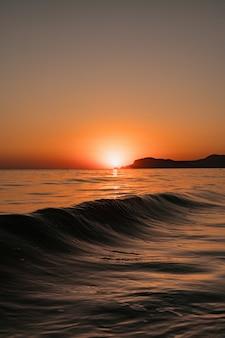 Vista do mar com céu claro e ondas ao pôr do sol