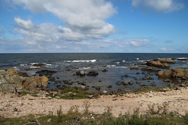 Vista do mar com grandes rochas e pedras na costa em hammer odde, bornholm, dinamarca