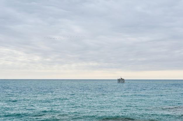 Vista do mar com instalação de aquicultura à distância e bando de pássaros no céu nublado