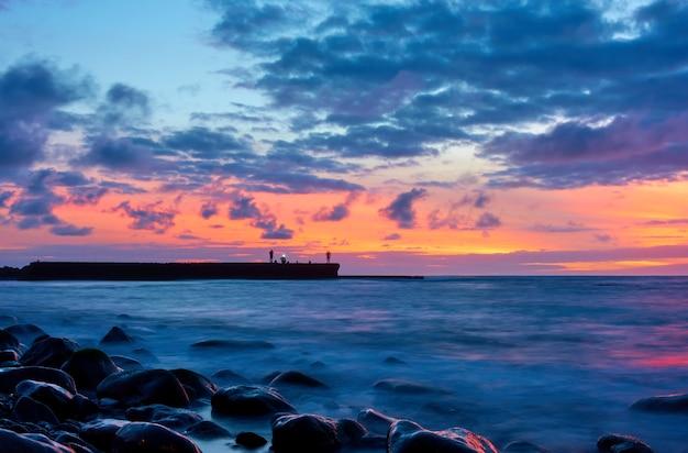Vista do mar com o oceano atlântico e o céu ao entardecer, pedras na praia e pescadores no cais. exposição longa com água do mar turva