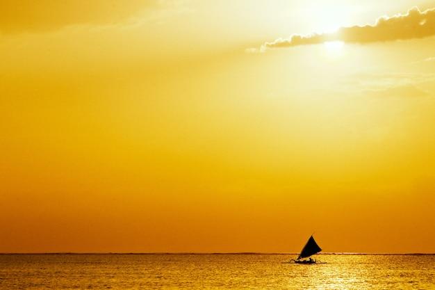 Vista do mar com pôr do sol dourado e um veleiro no meio do oceano