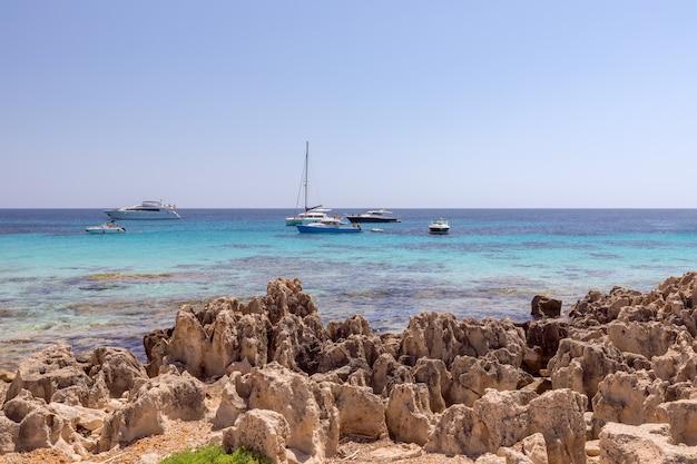Vista do mar com praia rochosa e mar esmeralda com iates