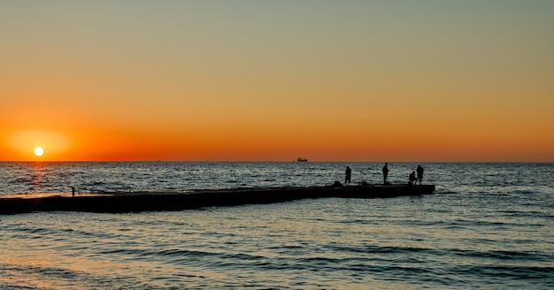 Vista do mar com um cais ao nascer do sol. pescadores à beira-mar.