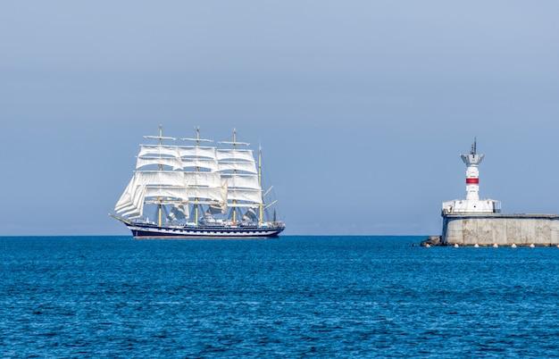 Vista do mar com veleiro branco e farol