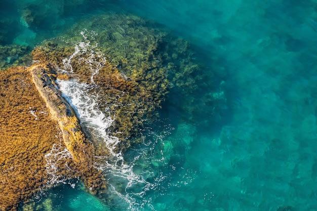 Vista do mar de águas cristalinas com pedras